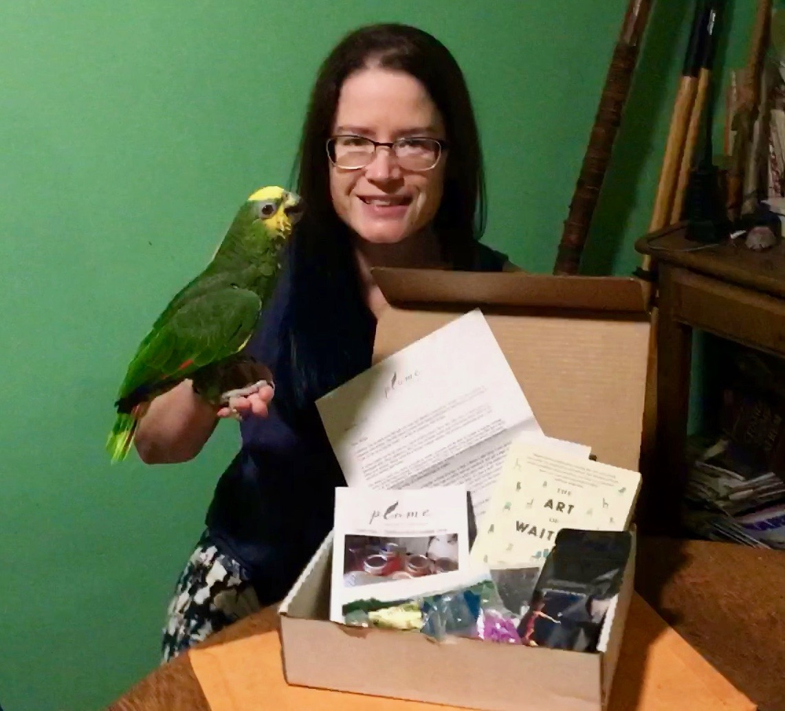 Elizabeth with her parrot looking at a box of treats from Plume for Writers